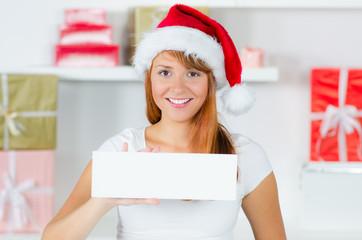 frau mit weihnachtsmütze zeigt  werbehinweis