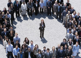 Portrait of businesswoman standing at center of circle formed by business people