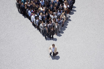 Businessman at apex of pyramid formed by crowd