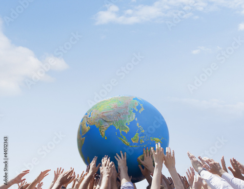 Crowd reaching for globe
