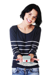 Beautiful young woman holding US dollars bills and house model