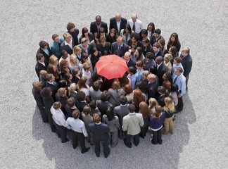 Umbrella at center of circle formed by business people