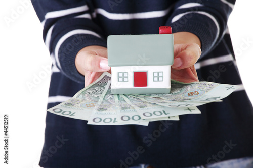 Woman holding PLN bills and house model over white.
