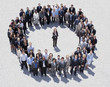 Portrait of woman standing at center of circle formed by business people