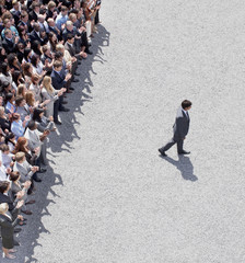 Businessman walking away from clapping crowd
