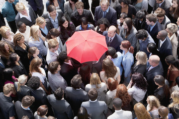 Red umbrella at center of business people in huddle