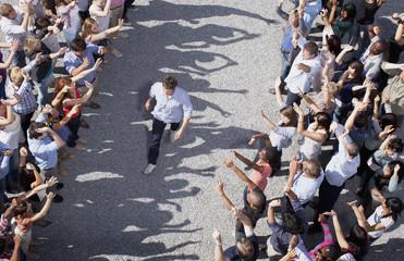 Man walking through cheering crowd