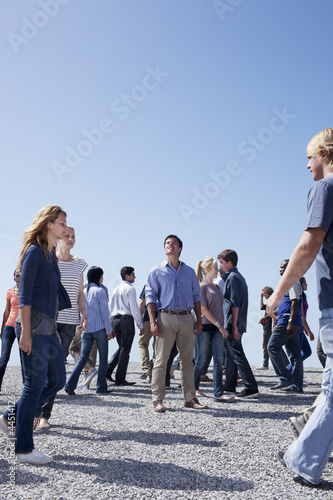 Man standing and looking up among crowd of walking people