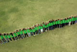 Portrait of people in green t-shirts standing in a row with arms raised in field