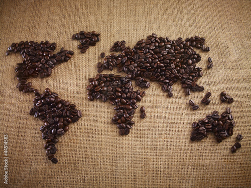 Coffee beans forming world map on burlap