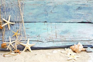 Strandgut vor blauem Holz mit Fischernetz