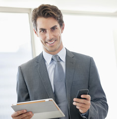 Portrait of smiling businessman holding cell phone and digital tablet