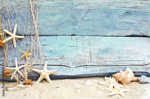 Leinwandbild Motiv Strandgut vor blauem Holz mit Fischernetz