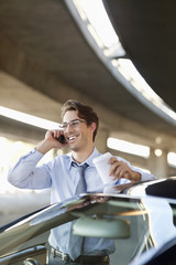 Smiling businessman talking on cell phone and holding coffee cup