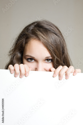 Beautiful brunette teen hiding behind sign.