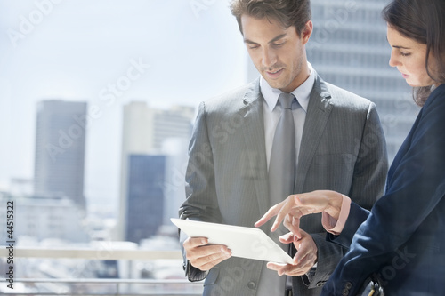 Businessman and businesswoman with digital tablet on urban balcony