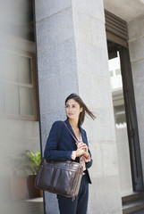 Businesswoman with briefcase in front of urban building