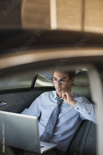 Businessman working on laptop in back seat of car at night