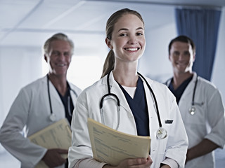 Portrait of smiling doctors holding medical records in hospital