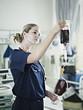 Nurse adjusting blood bag in hospital room