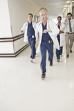 Doctors rushing down hospital corridor