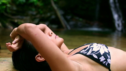 sexy girl with bikini lying down in waterfall river