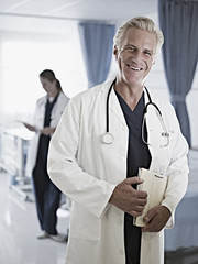 Portrait of confident doctor holding medical record in hospital
