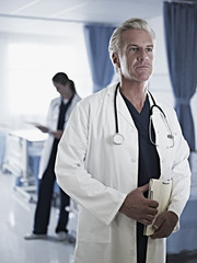 Serious doctor holding medical record in hospital room