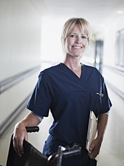 Serious nurse standing in hospital corridor with medical record and wheelchair
