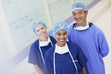 Portrait of smiling surgeon and nurses in hospital corridor