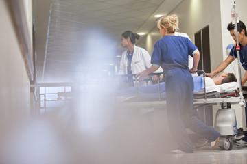 Doctors and nurses wheeling patient in