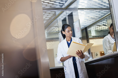 Doctor reviewing medical record in hospital elevator