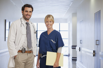Portrait of smiling doctor and nurse in hospital corridor