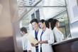 Smiling doctors reviewing medical record in hospital elevator