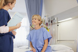Nurse with medical record talking to patient in hospital room