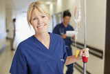 Portrait of smiling nurse with IV drip in hospital corridor