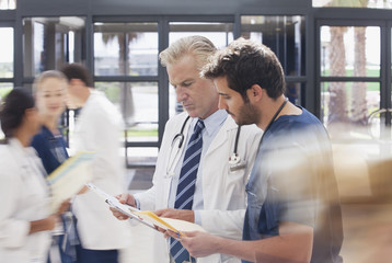 Doctor and nurse reviewing medical record in hospital