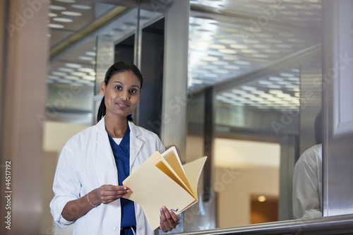 Portrait of confident doctor holding medical record in hospital elevator