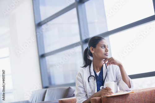 Pensive doctor drinking coffee and looking out window