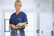 Portrait of smiling nurse holding medical record in hospital corridor
