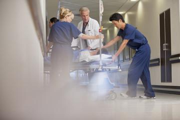 Doctors and nurses wheeling patient on gurney in hospital corridor