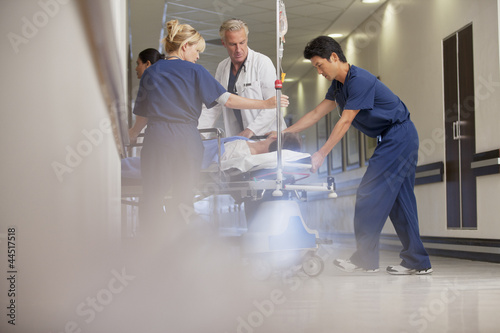 Doctors and nurses wheeling patient on gurney in hospital corridor