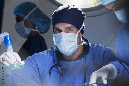 Portrait of serious surgeon holding oxygen mask in operating room