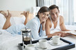 Portrait of smiling couple laying in bed with coffee