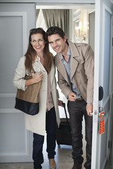 Smiling couple opening hotel room door