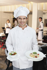 Portrait of smiling chef holding salad and entree