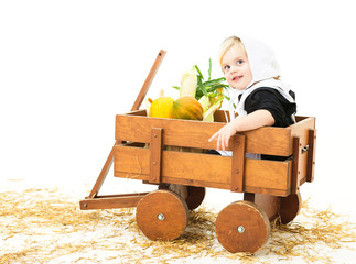 Pilgrim child sitting in a wagon with harvest produce.