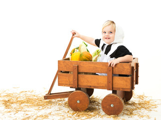cute little pilgrim girl in a wagon full of Fall vegetables