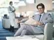 Portrait of smiling businessman reading newspaper in lounge