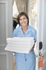Portrait of smiling maid with towels in hotel room doorway